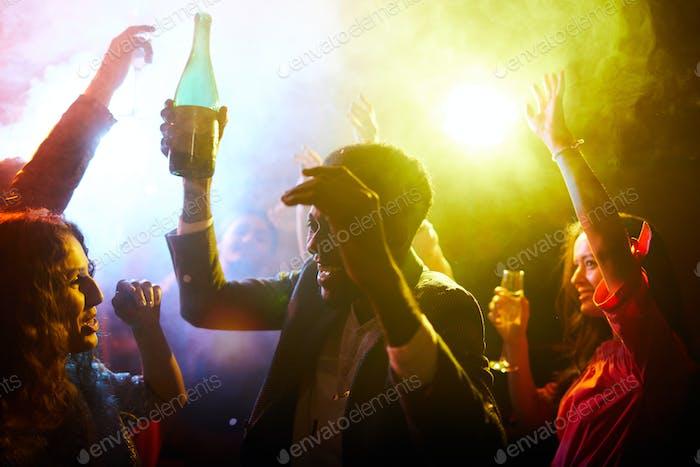 Jovial people dancing in smoke