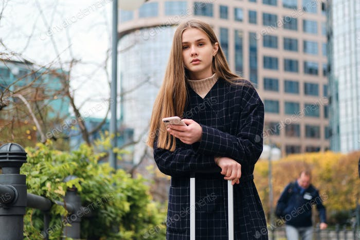 Beautiful casual girl in coat using cellphone while standing on city street with suitcase