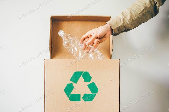 Werfen Sie Plastikflasche in die Recyclingbox.