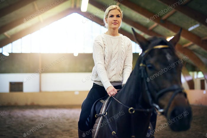 Female sitting astride in indoor riding hall