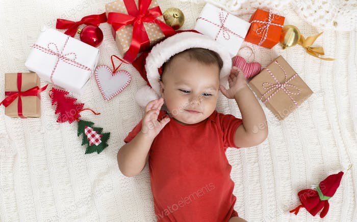 Adorable baby in Santa hat napping with Xmas gifts