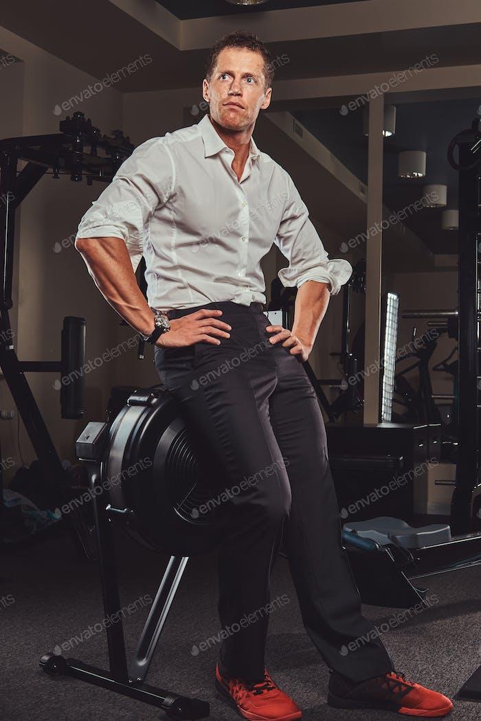 Schöner Geschäftsmann in formeller Kleidung kam nach einem anstrengenden Arbeitstag zum Training in die Turnhalle.
