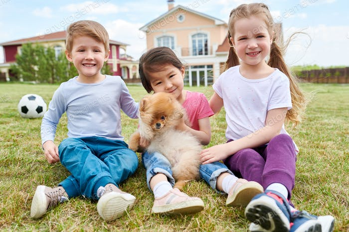 Happy Kids Playing with Puppy