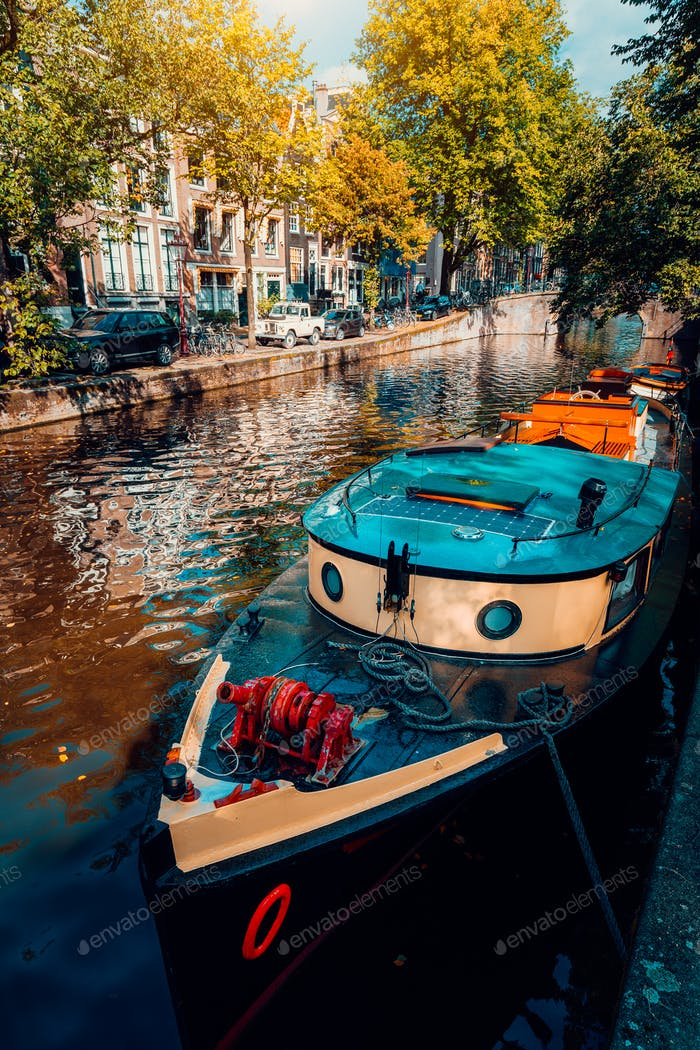 Traditional cruising tour boat moored tied up in one of the famous Amsterdam canals on the beautiful