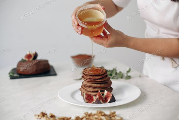 Cook pours honey on the pancakes.
