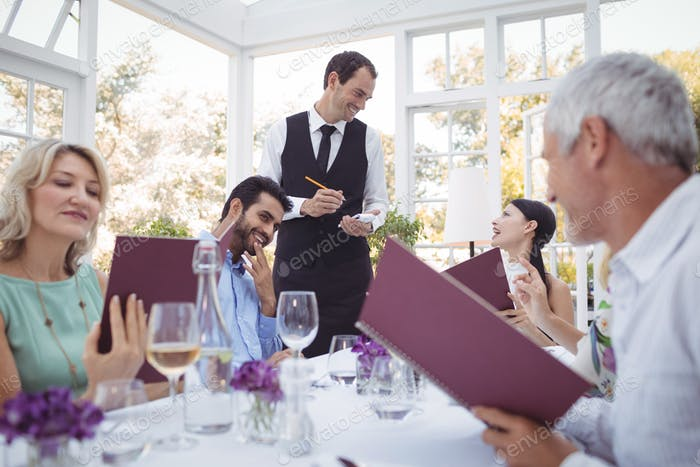 Friends placing order to waiter