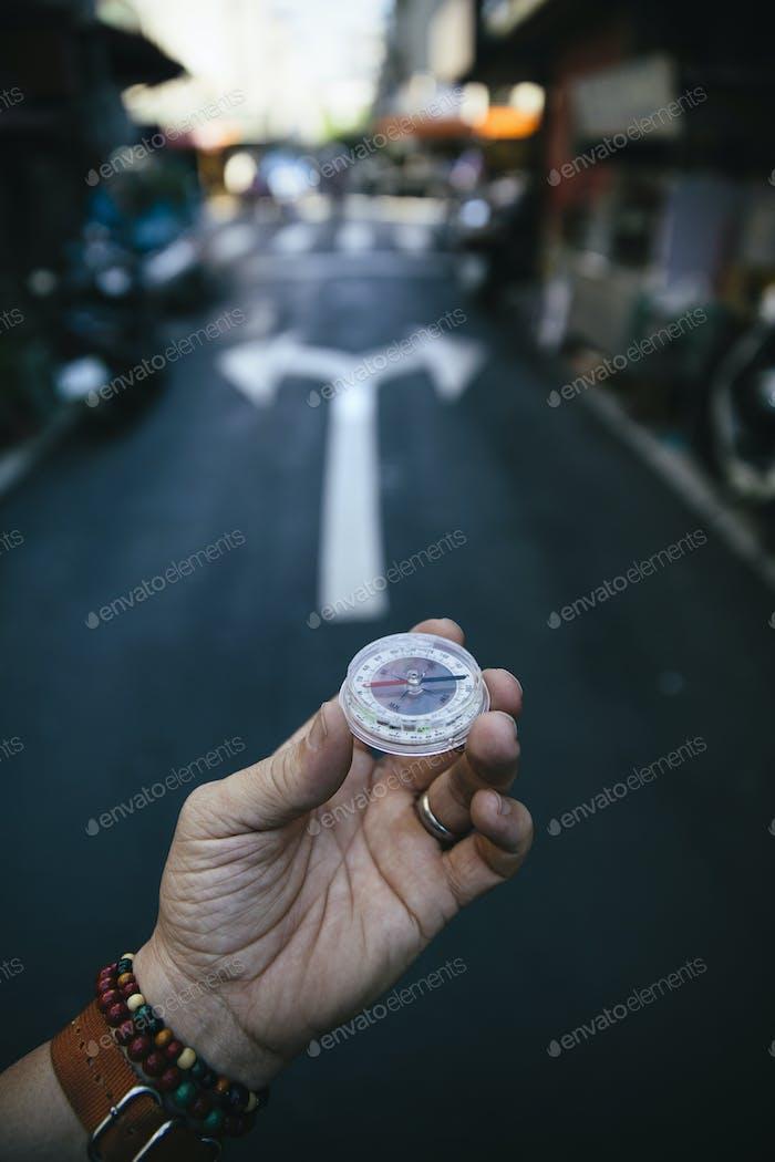 Eine Hand, die einen Kompass an einer Kreuzung auf einer Stadtstraße hält.