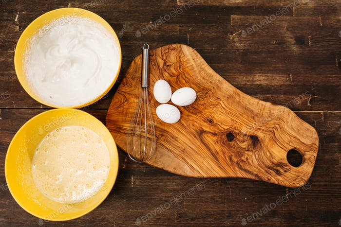 Eggs on wooden board, bowls with cake ingredients