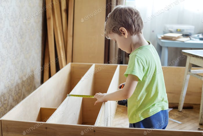 Young boy using reel to measure wooden shelf of bookcase