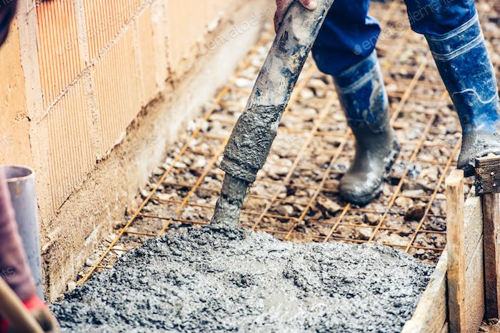 close up of industrial worker pouring cement or concrete with automatic pump tube