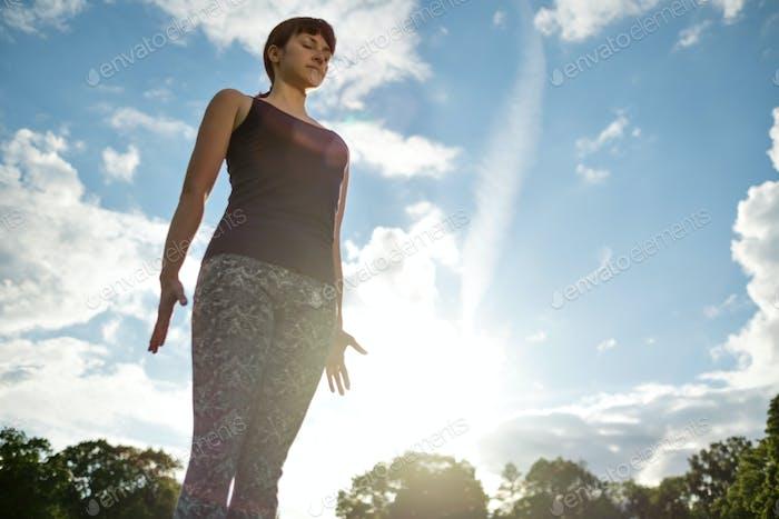 Yoga outdoor in park. Woman doing yoga exercises.Mountain yoga pose tadasana.