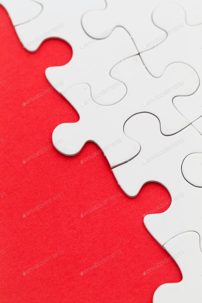 Blank white jigsaw puzzles on a bright red paper background