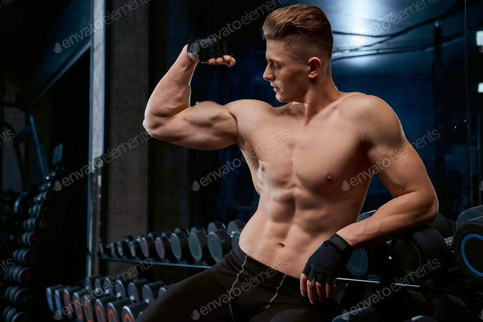 Shirtless bodybuilder posing in gym