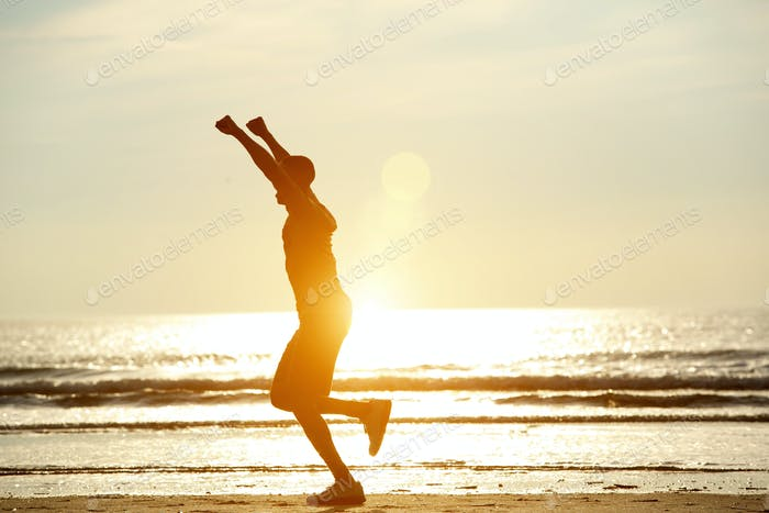 One man running on beach with arms raised
