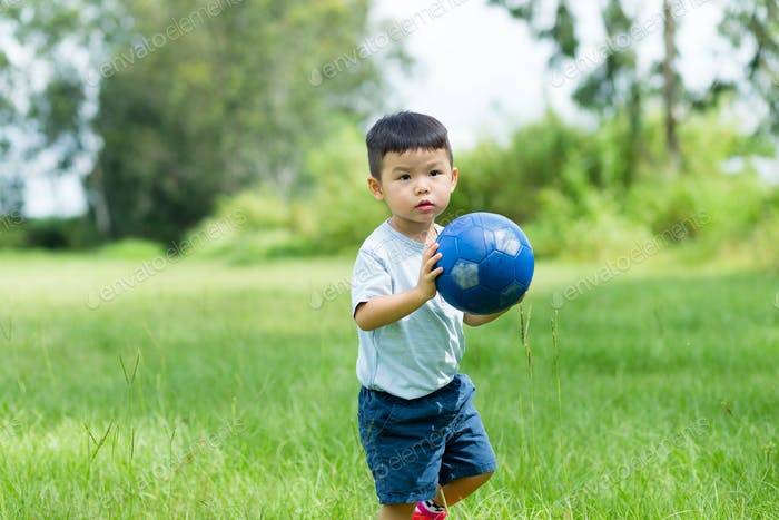 Little boy play football at outdoor