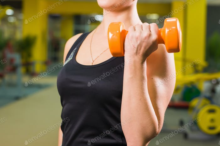 fit girl exercising with dumbbells. Muscular woman lifting weights