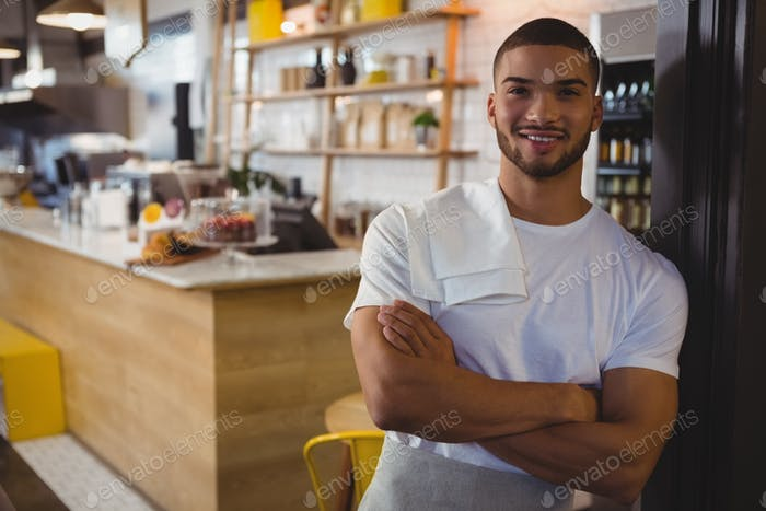 Portrait of waiter standing in cafe