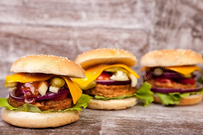 Delicious tasty burgers on wooden background