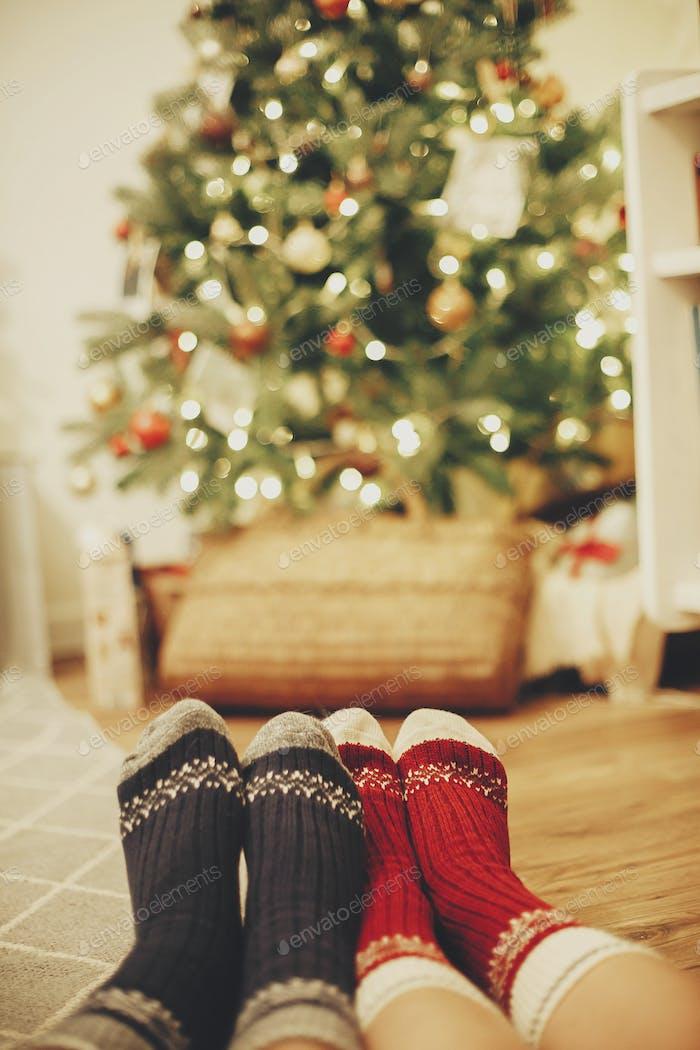 Stylish festive socks on couple legs on background