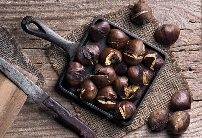 pan full of roasted chestnuts on rustic wood