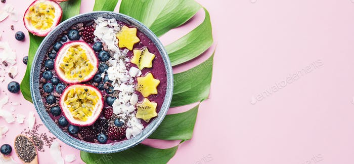 Smoothie acai bowl served in bowl on pink table