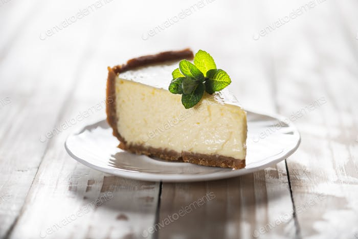 Slice of New York cheesecake with a sprig of mint