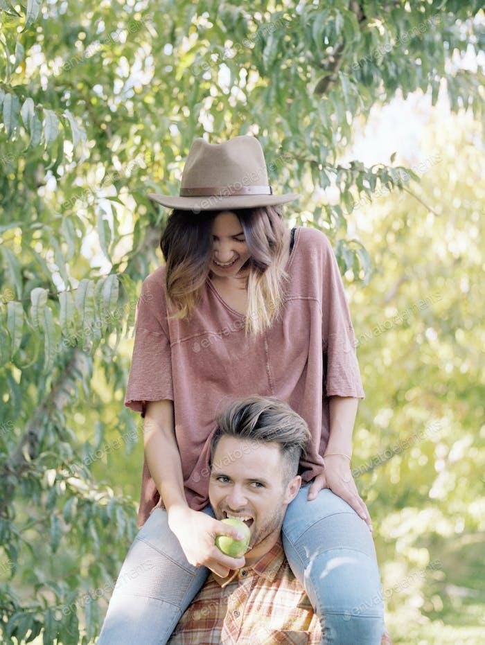 Apfelplantagen. Mann trägt eine Frau auf seinen Schultern, isst einen Apfel.