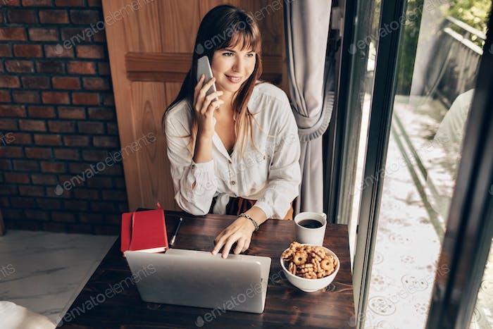 Happy freelance trabajadora sentada en casa con taza de café