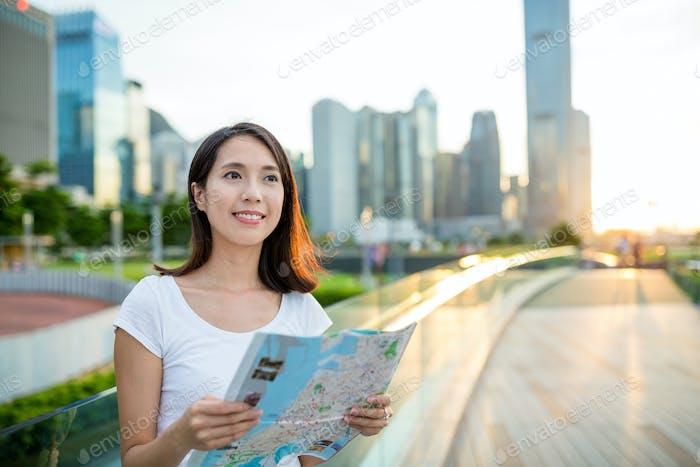 Mujer comprobando mapa de papel bajo el atardecer