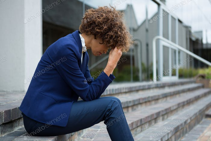 Depressed businesswoman sitting in the premises