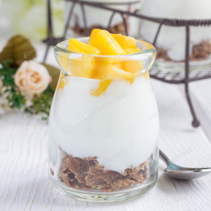 Breakfast dessert with bran flakes, plain yogurt and mango, square