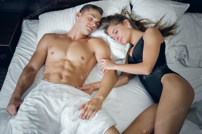 Attractive young couple lying on a bed.
