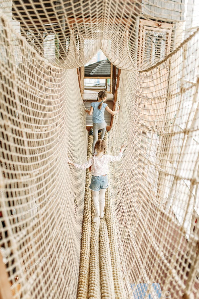 Two girls plays in rope net, children game center