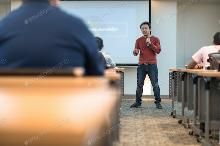 Asian speaker showing and presenting the knowledge in front of the stage