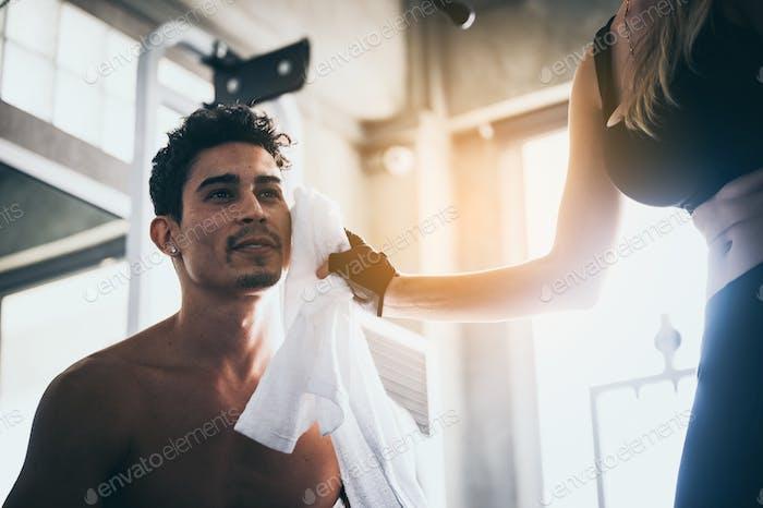 Das Mädchen benutzt ein Taschentuch, um den jungen Mann während des Trainings im Fitnessstudio zu schwitzen.