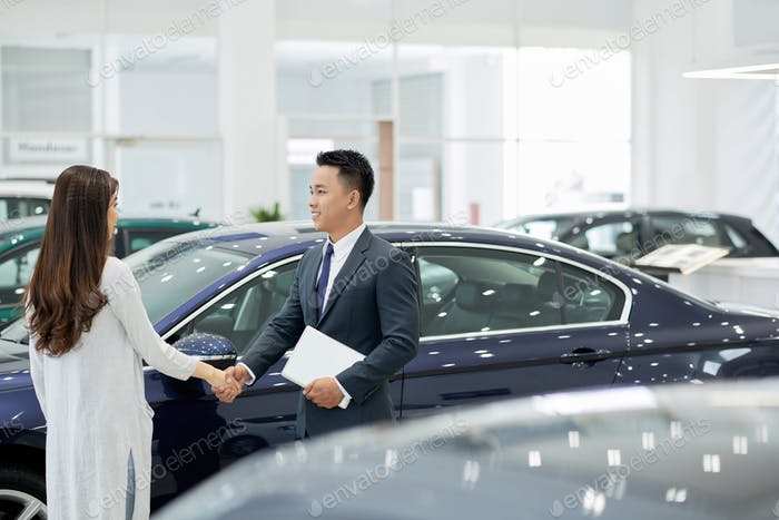 Salesman and client in car showroom