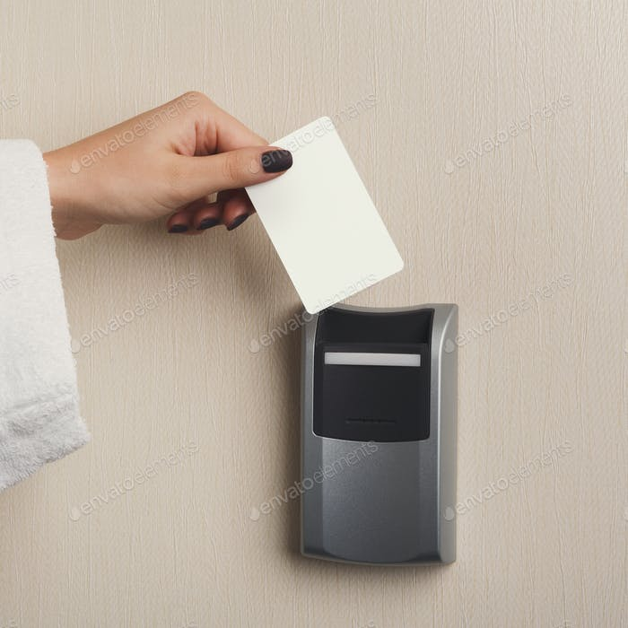 Hand inserting key card in electronic lock