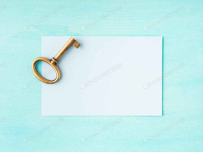 Vintage brass key and empty paper card