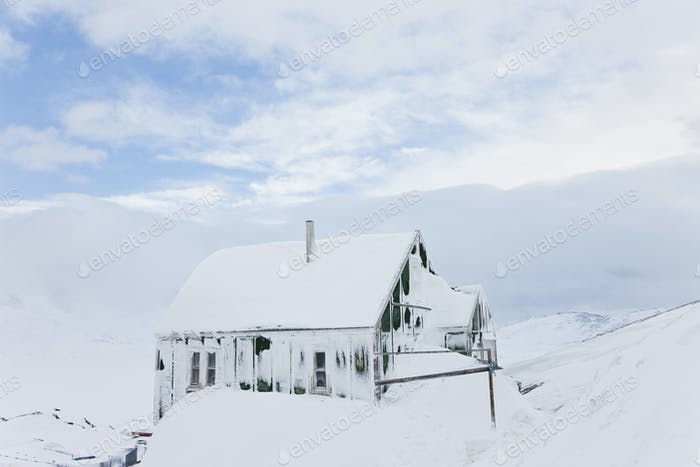 Winter landscape with wooden, snow-covered cottage under a cloudy sky.