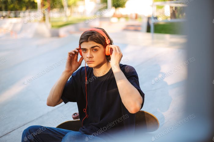 Young guy in orange headphones thoughtfully looking in camera wh