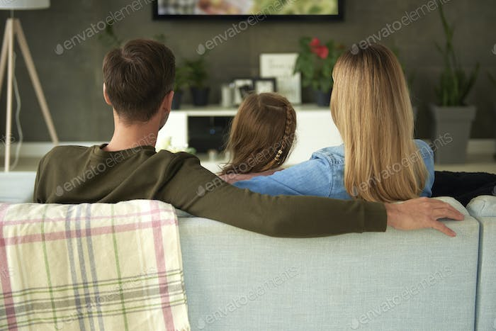 Rear view of family with one child watching tv