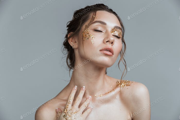 Brunette woman with soft healthy skin and golden makeup
