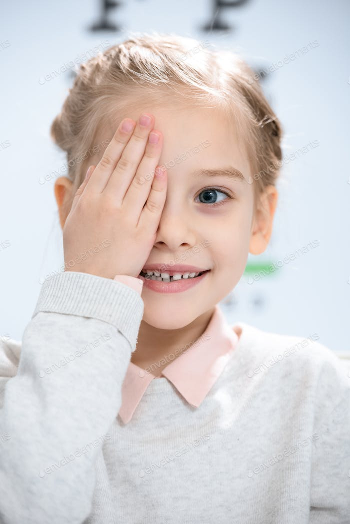 smiling little kid closing eye with eye chart behind