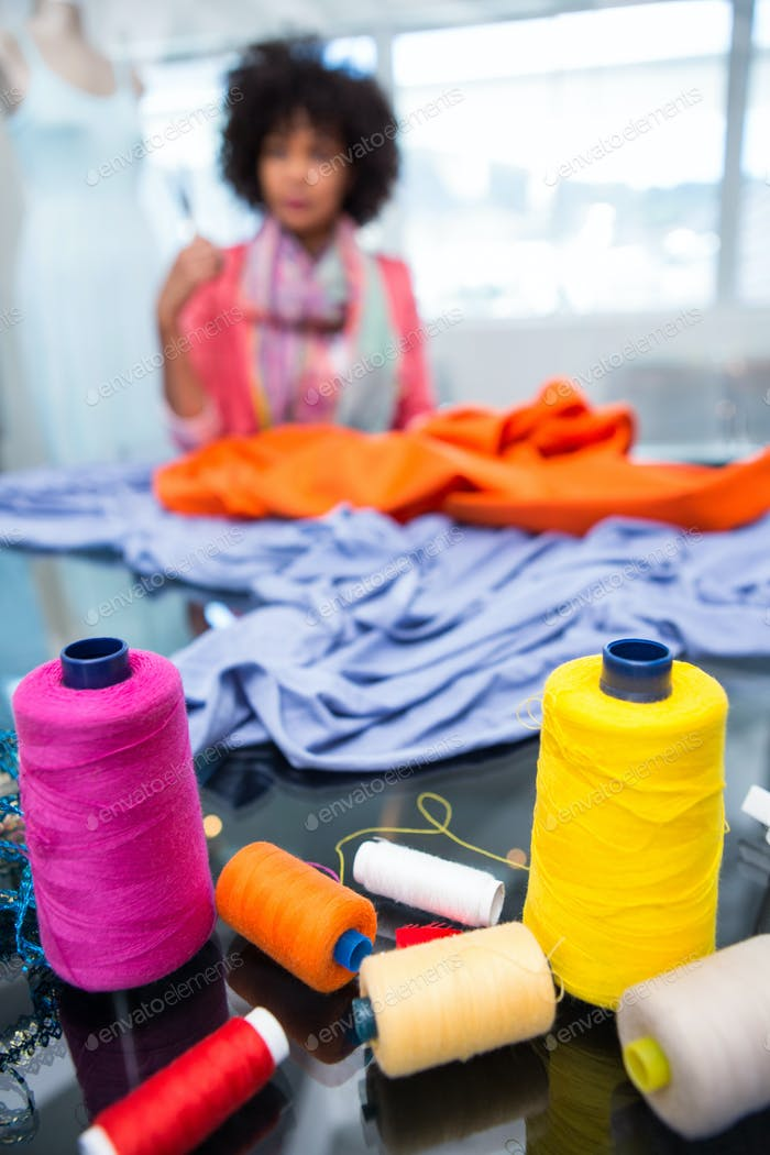 Close up of threads on table with female fashion designer in background