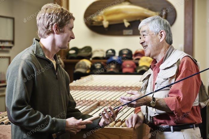 Männlicher Besitzer eines Einzelhandelsgeschäfts Fliegenfischen im Gespräch mit einem jungen kaukasischen Kunden-Sharing-Know-how