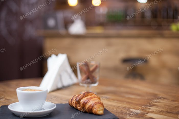 Delicious croissant served with a warm cup of coffee