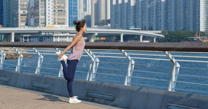 Frau strecken Beine vor dem Laufen im Freien