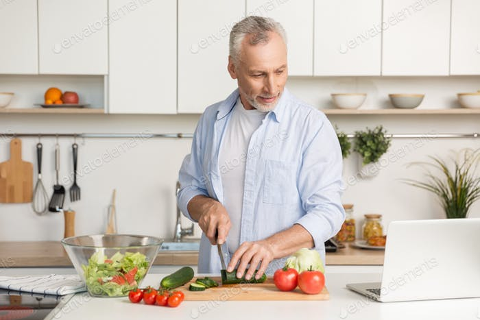 Handsome man standing at the kitchen using laptop and cooking