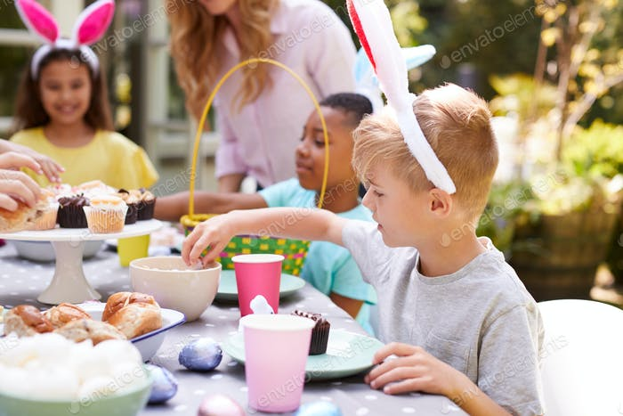 Mother With Children Wearing Bunny Ears Enjoying Outdoor Easter Party In Garden At Home