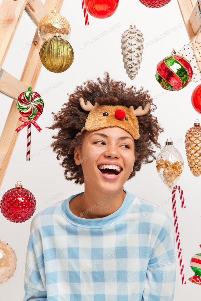 Happy moments and celebration concept. Joyful dark skinned young woman laughs positively shows white